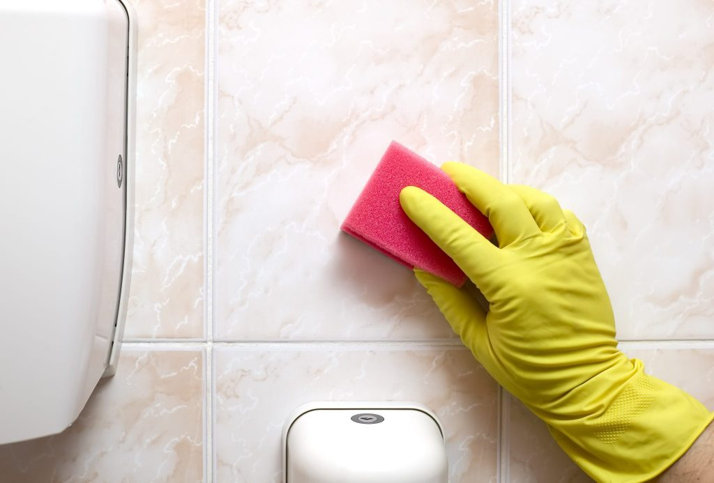 Scrubbing Bathroom Wall with Sponge